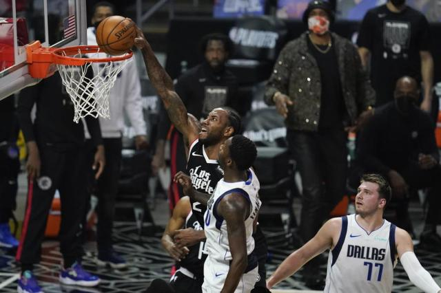 Los Angeles Clippers forward Kawhi Leonard (2) dunks against Dallas Mavericks forward Dorian Finney-Smith (10) during the first quarter of Game 7 of an NBA basketball first-round playoff series Sunday, June 6, 2021, in Los Angeles, Calif. Mavericks guard Luka Doncic (77) looks on. (AP Photo/Ashley Landis)