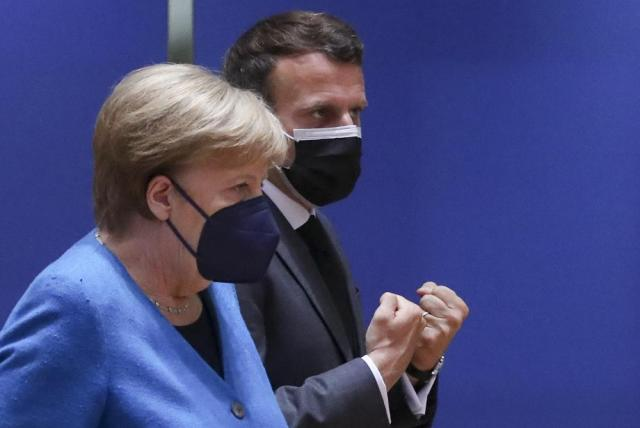 German Chancellor Angela Merkel, left, speaks with French President Emmanuel Macron during a round table meeting at an EU summit in Brussels, Monday, May 24, 2021. European Union leaders are expected, during a two day in-person meeting, to focus on foreign relations, including Russia and the UK. (Yves Herman, Pool via AP)