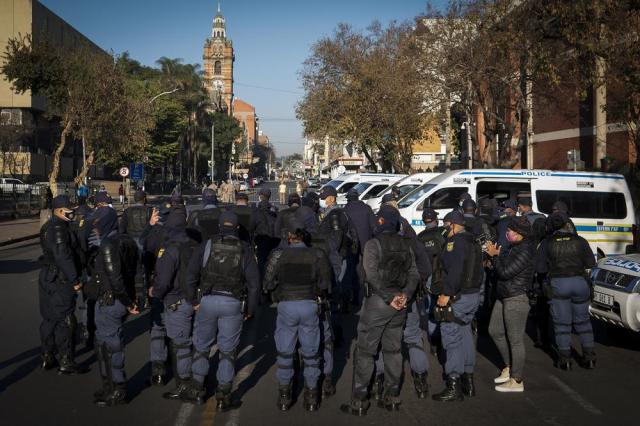 Members of the South African Police Services on patrol outside the High Court in Pietermaritzburg, South Africa, Monday July 19, 2021, where the corruption trial of former South African President Jacob Zuma resumed. The trial continued more than a week after Zuma's imprisonment for contempt of court in a separate case set off rioting. (AP Photo/Shiraaz Mohamed)