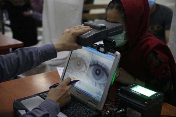 Un empleado toma los datos biométricos a una mujer que tramita su pasaporte en Kabul el 30 de junio del 2021. (AP Photo/Rahmat Gul, File)