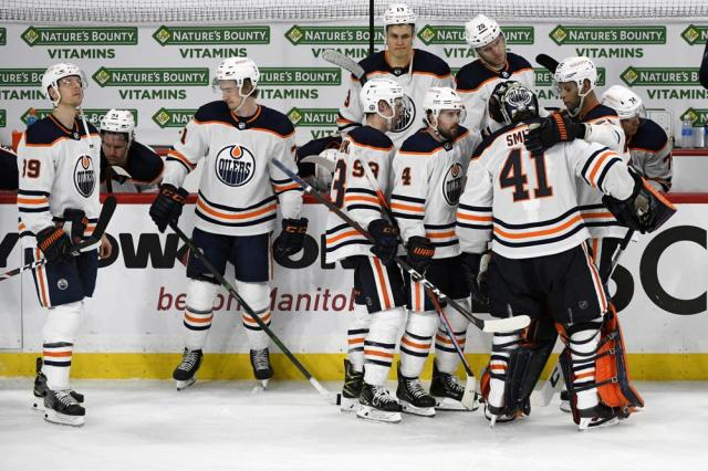 Edmonton Oilers console goaltender Mike Smith (41) after he allowed the game-winning goal during third overtime period of an NHL hockey Stanley Cup playoff game, Monday, May 24, 2021, in Winnipeg, Manitoba. (Fred Greenslade/The Canadian Press via AP)