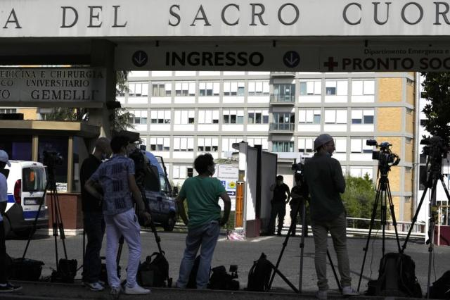 Members of the media stand at the entrance of Rome's Gemelli Polyclinic where Pope Francis has been hospitalized for a for scheduled surgery for a stenosis, or restriction, of the large intestine, the Vatican said, Sunday, July 4, 2021. The news came just three hours after Francis had cheerfully greeted the public in St. Peter's Square and told them he will go to Hungary and Slovakia in September.  (AP Photo/Alessandra Tarantino)