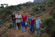 """Una familia posa para una foto en el sitio donde se encontraba su casa, destruida por un derrumbe provocado la deforestación y dos huracanes en La Reina, Honduras. Foto del 24 de junio del 2021. De izq. a der.: Melvin Alonso (de 14 años), Guillermo Alonso (54), Elvin Alonso (seis meses), Génesis Alonso (6), María Orellana (52), Yenny Alonso (16), Areli Alonso (22) y Orlin Alonso (25). """"Nos entristece porque nos quedamos sin casa, pero lo importante es que toda la familia está viva"""", dijo Guillermo. (AP Photo/Rodrigo Abd)"""