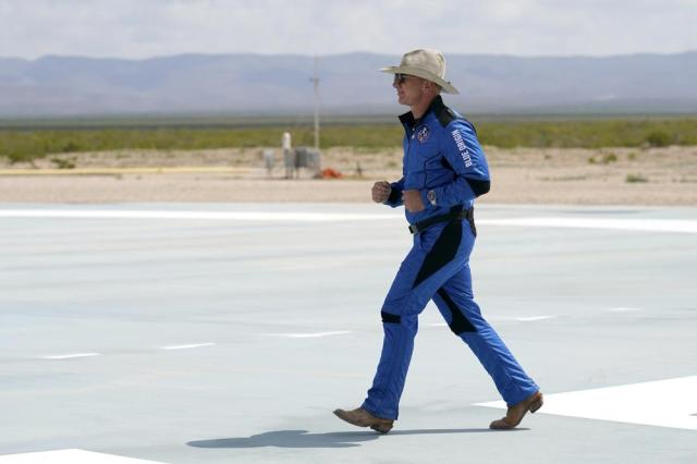 Jeff Bezos, founder of Amazon and space tourism company Blue Origin jogs onto the Blue Origin's New Shepard rocket landing pad to pose for photos at the spaceport near Van Horn, Texas, Tuesday, July 20, 2021. (AP Photo/Tony Gutierrez)