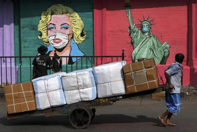 FILE - In this Friday, March. 26, 2021 file photo, a laborer carrying goods on his handcart looks at an artist painting a mural of Marilyn Monroe and the Statue of Liberty wearing face masks to spread awareness for the prevention of the coronavirus in Mumbai, India. (AP Photo/Rajanish Kakade)