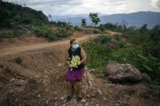 Dilma Murillo, de 63 años, se sienta en una piedra en el lugar donde estuvo su casa antes de ser destruída por un deslave provocado por el paso de los huracanes Eta e Iota en la comunidad de La Reina, Honduras, el martes 22 de junio de 2021. (AP Foto/Rodrigo Abd)