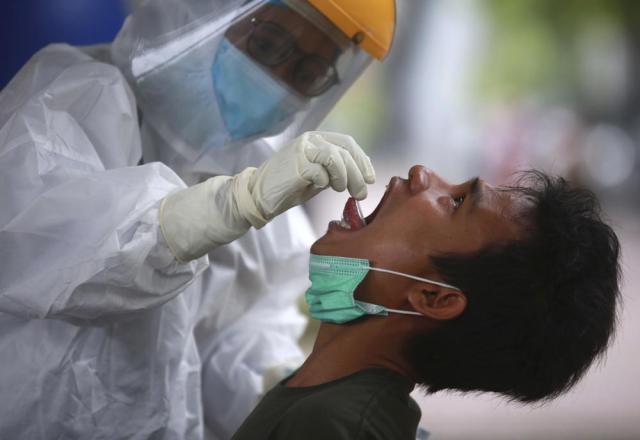 A man reacts as a medical worker collects his nasal swab samples during a mass test for the coronavirus at North Sumatra University (USU) Hospital in Medan, North Sumatra, Indonesia, Wednesday, June 2, 2021. (AP Photo/Binsar Bakkara)