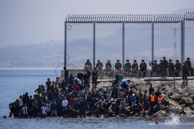 Migrants wait to cross into the Spanish enclave of Ceuta, near the border of Morocco and Spain, on Tuesday, May 18, 2021. About 8,000 people have streamed into the Spanish city of Ceuta from Morocco in the past two days in an unprecedented influx of migrants, most of them swimming across the border to reach the Spanish enclave in North Africa. (AP Photo/Bernat Armangue)