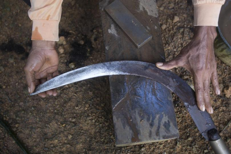 An Indonesian migrant worker sharpens the blade of his sickle used for cutting down palm oil fruit from tall trees in Sabah, Malaysia, on Monday, Dec. 10, 2018. Many Indonesians working in Malaysia do not have proper documents, leaving them vulnerable to exploitation, arrest or deportation. (AP Photo/Binsar Bakkara)