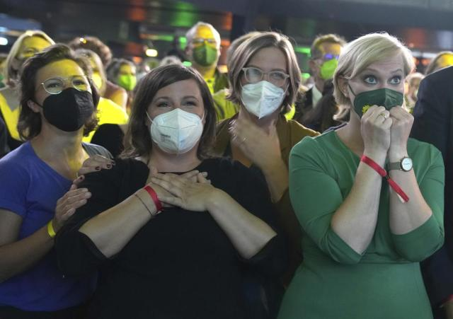 Guests at the election party of the Greens react after the publication of the first forecasts on the outcome of the 2021 federal election in Berlin, Sunday, Sept. 26, 2021. Exit polls show the center-left Social Democrats in a very close race with outgoing Chancellor Angela Merkel's bloc in Germany's parliamentary election, which will determine who succeeds the longtime leader after 16 years in power.  (Kay Nietfeld/dpa via AP)