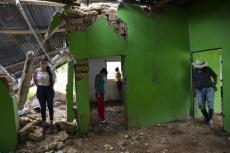 De izquierda a derecha, Marian Castrón, de 23 años; María Castrón, de 25; Jenny Castrón, de 19, y Omar Castrón, de 50, visitan lo que quedó de su casa devastada por un deslave provocado por el paso en noviembre de 2020 de los huracanes Eta e Iota en la comunidad de La Reina, Honduras, el viernes 25 de junio de 2021. (AP Foto/Rodrigo Abd)