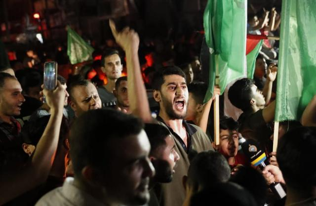 Palestinians chant slogans as they wave green Hamas and their national flags while celebrating the cease-fire agreement between Israel and Hamas in Gaza City, early Friday, May 21, 2021. (AP Photo/Adel Hana)