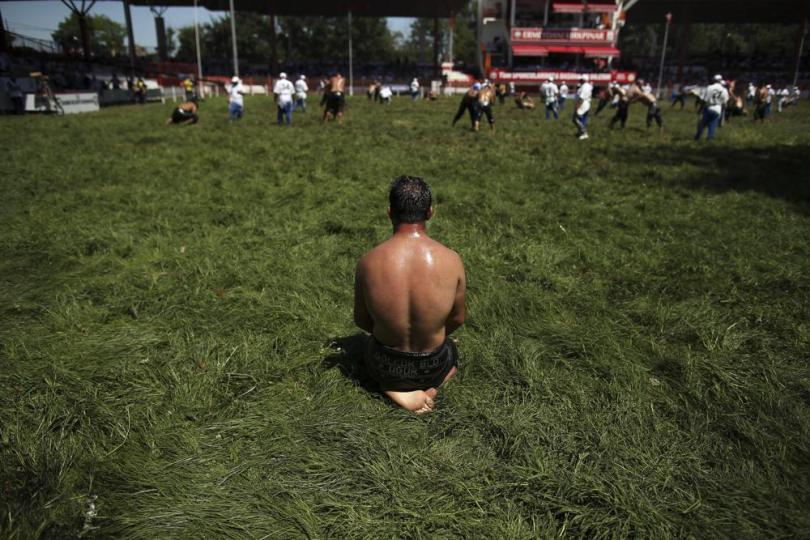 A wrestler, doused in olive oil, watches as others compete on the third and last day of the 660th instalment of the annual Historic Kirkpinar Oil Wrestling championship, in Edirne, northwestern Turkey, Sunday, July 11, 2021.Thousands of Turkish wrestling fans flocked to the country's Greek border province to watch the championship of the sport that dates to the 14th century, after last year's contest was cancelled due to the coronavirus pandemic. The festival, one of the world's oldest wrestling events, was listed as an intangible cultural heritage event by UNESCO in 2010. (AP Photo/Emrah Gurel)