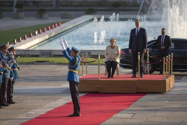 German Chancellor Angela Merkel, center, listens to the honor guard brass band as they play while being accompanied by Serbia's president Aleksandar Vucic, second right, during her visit to Belgrade, Serbia, Monday, Sept. 13, 2021. Merkel is on a farewell tour of the Western Balkans, as she announced in 2018 that she wouldn't seek a fifth term as Germany's Chancellor. (AP Photo/Marko Drobnjakovic)