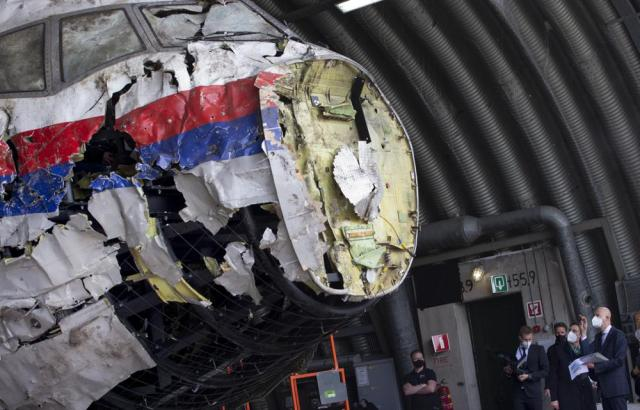 Presiding judge Hendrik Steenhuis, far right, points as he and other trial judges and lawyers view the reconstructed wreckage of Malaysia Airlines Flight MH17, at the Gilze-Rijen military airbase, southern Netherlands, Wednesday, May 26, 2021. (AP Photo/Peter Dejong, Pool)