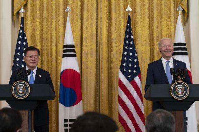 South Korean President Moon Jae-in, left, smiles with President Joe Biden during a joint news conference in the East Room of the White House, Friday, May 21, 2021, in Washington. (AP Photo/Alex Brandon)