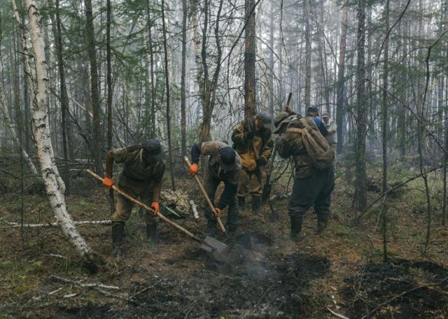 Volunteers and employees of the Yakutlesresurs dig a moat to stop a forest fire outside Magaras village 87 km. (61 miles) west of Yakustk, the capital of the republic of Sakha also known as Yakutia, Russia Far East, Sunday, July 18, 2021. Russia has been plagued by widespread forest fires, blamed on unusually high temperatures and the neglect of fire safety rules, with the Sakha-Yakutia region in northeastern Siberia being the worst affected. (AP Photo/Alexey Vasilyev)
