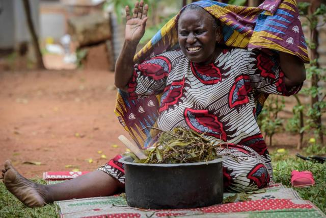 A woman reacts after covering herself to inhale steam from an infusion made from local herbs believed by her to prevent and treat the symptoms of COVID-19, in Kampala, Uganda Tuesday, July 6, 2021. Some hospitals with COVID-19 wards are charging prohibitive sums for most Ugandans and many are now self-medicating within their homes, experimenting with everything from traditional medicine to a newly approved herbal remedy selling briskly as COVIDEX. (AP Photo/Nicholas Bamulanzeki)