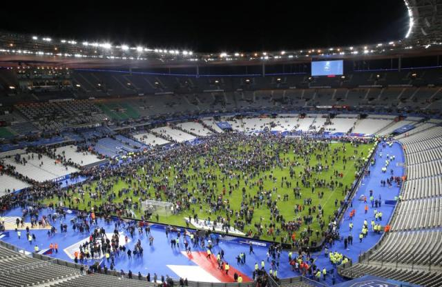 FILE - In this Nov.13, 2015 file photo, spectators invade the pitch of the Stade de France stadium after the international friendly soccer France against Germany, in Saint Denis, outside Paris. On Nov. 13, 2015, a cell of nine Islamic State militants armed with automatic rifles and explosive vests left a trail of dead and injured at the national stadium, Paris bars and restaurants and the Bataclan concert hall. (AP Photo/Michel Euler, File)