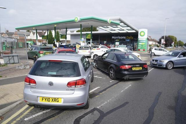 Cars queue outside a petrol station in Leicester, England, Saturday Sept. 25, 2021. The haulage industry says the U.K. is short tens of thousands of truckers, due to a perfect storm of factors including the coronavirus pandemic, an aging workforce and an exodus of European Union workers following Britain's departure from the bloc. BP and Esso shut a handful of their gas stations this week, and motorists have formed long lines as they try to fill up in case of further disruption. (Mike Egerton//PA via AP)