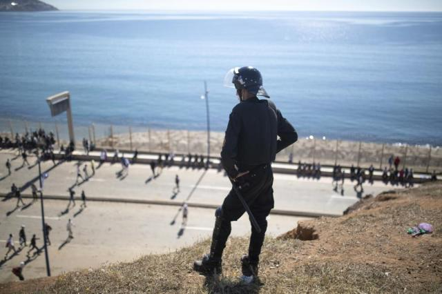 A member of Moroccan security forces stands guard at a hill overlooking the border of Morocco and Spain as Moroccan and sub-saharan migrants attempt to enter the Spanish enclave of Ceuta, on Wednesday, May 19, 2021.  Spain's north African enclave of Ceuta has awakened to a humanitarian crisis after thousands of migrants who crossed over from Morocco spent the night sleeping where they could find shelter. (AP Photo/Mosa'ab Elshamy)