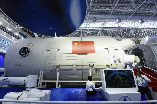 In this Nov. 7, 2018 photo, visitors look at a life-size model of the Tianhe core module of China's next space station at the Airshow China in Zhuhai in southern China's Guangdong Province. China on Thursday, June 17, 2021 has launched its first crewed space mission in five years, sending three astronauts to a new space station that marks a milestone in the country's ambitious space program. (Chinatopix via AP)
