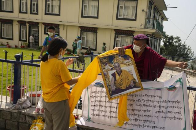 An exile Tibetan monk removes a portrait of his spiritual leader the Dalai Lama as he celebrates the 86th birthday of the Tibetan leader in Dharmsala, India, Tuesday, July 6, 2021. The Dalai Lama made the hillside town of Dharmsala his headquarters after a failed uprising against Chinese rule in 1959.(AP Photo/Ashwini Bhatia)