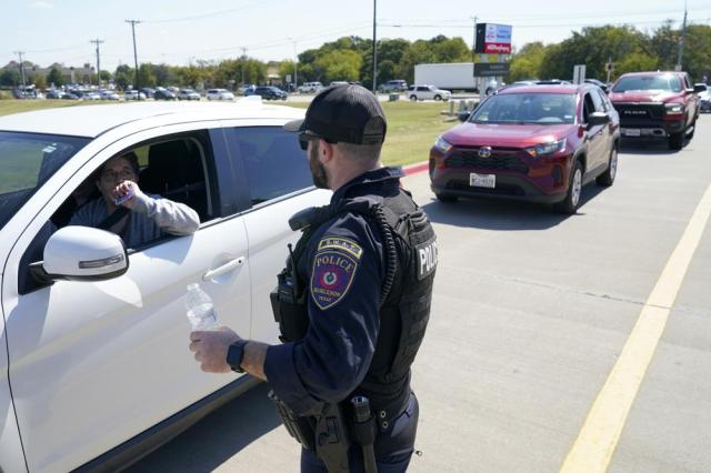 A Burleson, Texas, SWAT officer directs traffic to a parking area for families arriving to be reunited with their school children, Wednesday, Oct. 6, 2021 in Mansfield, Texas, following a shooting at Timberview High School in Arlington. (AP Photo/Tony Gutierrez)