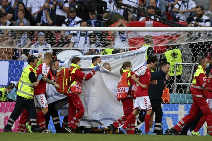 Denmark's Christian Eriksen is taken away on a stretcher after collapsing on the pitch during the Euro 2020 soccer championship group B match between Denmark and Finland at Parken Stadium in Copenhagen, Saturday, June 12, 2021. (Stuart Franklin/Pool via AP)