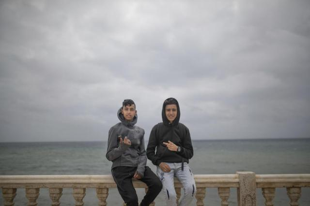 """Ayoub and Khalid pose for a photo as they wait for a chance to cross the Spanish enclave of Ceuta from the northern town of Fnideq, Morocco, Thursday, May 20, 2021. """"I am the eldest of my brothers, my mother sells vegetable in the market"""" and can't afford to support them, said Ayoub, in his early 20s, who arrived Thursday from the inland city of Meknes. """"I had to try and help my mother."""" (AP Photo/Mosa'ab Elshamy)"""