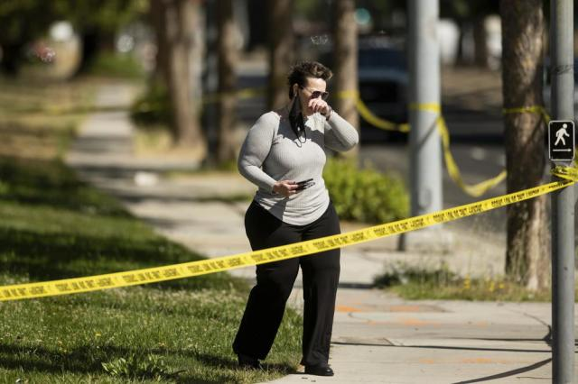 A woman leaves the scene of a shooting at a Santa Clara Valley Transportation Authority (VTA) facility on Wednesday, May 26, 2021, in San Jose, Calif. Santa Clara County sheriff's spokesman said the railyard shooting left multiple people, including the shooter, dead. (AP Photo/Noah Berger)