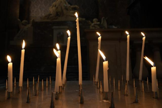 Candles are lighten in a Catholic Church in central Paris, Tuesday, Oct. 5, 2021. The head of France's Catholic bishops conference is asking forgiveness from the estimated 330,000 victims of child sex abuse by the church found in a groundbreaking report. The report was released Tuesday after extensive research in France's first major reckoning with the issue. (AP Photo/Francois Mori)