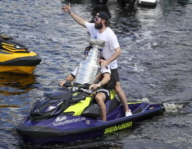 Tampa Bay Lightning left wing Alex Killorn drives a jet ski while holding the Stanley Cup as teammate Nikita Kucherov gestures to the crowd while celebrating the teams NHL hockey Stanley Cup victory with a boat parade Monday, July 12, 2021 in Tampa, Fla. (Dirk Shadd/Tampa Bay Times via AP)