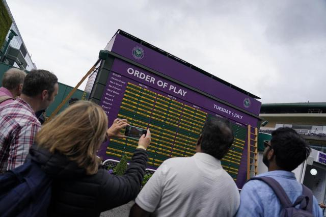 Spectators look at the order of play on day eight of the Wimbledon Tennis Championships in London, Tuesday, July 6, 2021. (AP Photo/Alberto Pezzali)