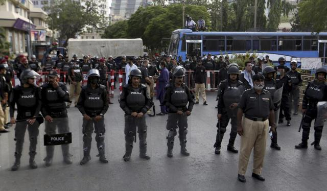 Police officers stand guard to stop the supporters of the Pakistani religious group' Jamaat-e-Islami' marching toward U.S consulate at rally in support of Palestinians, in Karachi, Pakistan, Friday, May 21, 2021. (AP Photo/Fareed Khan)
