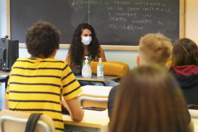 """A teacher and students wear face masks during a lesson, at the """"Isacco Newton"""" high school, in Rome, Monday, Sept. 13, 2021. After most of the last year spent with high schools in remote learning or lock-down, students are going back in classrooms, with all school workers having to present a so-called """"Green Pass"""" that proves they has received at least one vaccine dose in the last nine months, recovered from COVID-19 in the last six months or tested negative in the previous 48 hours, to access the institutes. (AP Photo/Andrew Medichini)"""