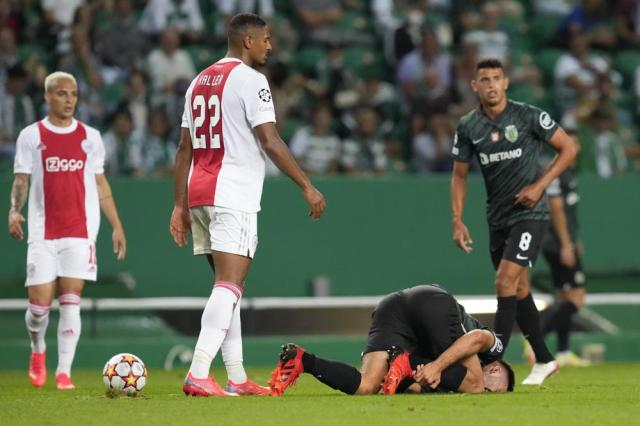 Sporting's Goncalo Inacio is on the ground after a clash with Ajax's Sebastien Haller, center left, during a Champions League, Group C soccer match between Sporting CP and Ajax at the Alvalade stadium in Lisbon, Wednesday, Sept. 15, 2021. (AP Photo/Armando Franca)