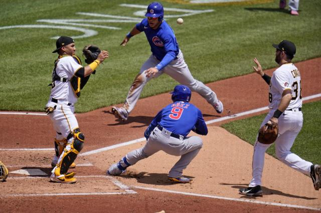 Pittsburgh Pirates first baseman Will Craig, right, tosses the ball to catcher Michael Perez, left, after Chicago Cubs' Javier Baez (9) hit a fielder's choice third to first and was caught in a rundown between home and first during the third inning of a baseball game in Pittsburgh, Thursday, May 27, 2021. Cub's Willson Contreras, top center, scores on the play and Báez reached second on an errant throw by Pirates' catcher Perez. (AP Photo/Gene J. Puskar)