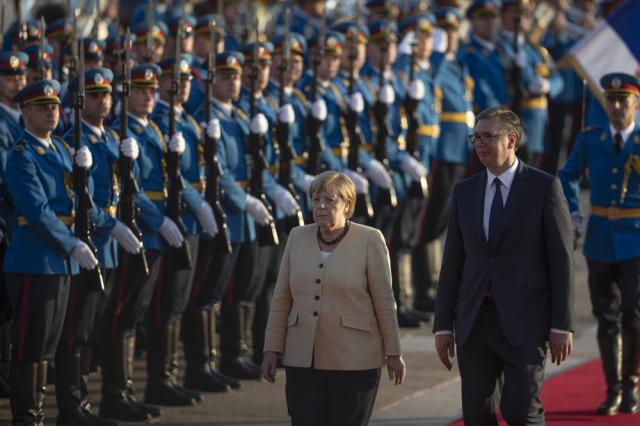 German Chancellor Angela Merkel, center, walks past honor guards while being accompanied by Serbia's president Aleksandar Vucic, front right, in Belgrade, Serbia, Monday, Sept. 13, 2021. Merkel is on a farewell tour of the Western Balkans, as she announced in 2018 that she wouldn't seek a fifth term as Germany's Chancellor. (AP Photo/Marko Drobnjakovic)