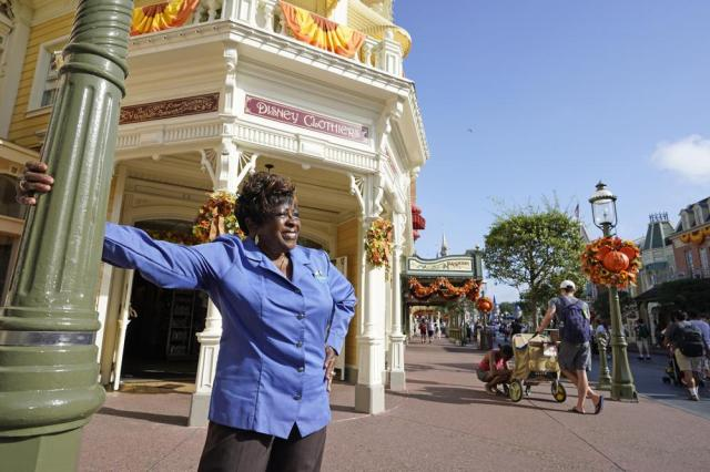 """Fifty-year employee Earliene Anderson stands on Main Street at the Magic Kingdom theme park at Walt Disney World Monday, Aug. 30, 2021, in Lake Buena Vista, Fla. """"Disney has been my love, and it still is,"""" Anderson said recently before starting her shift in merchandising. (AP Photo/John Raoux)"""