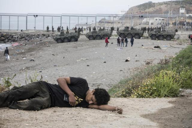 A man lies on the ground after arriving in the Spanish territory at the border of Morocco and Spain, at the Spanish enclave of Ceuta, on Tuesday, May 18, 2021. (AP Photo/Javier Fergo)