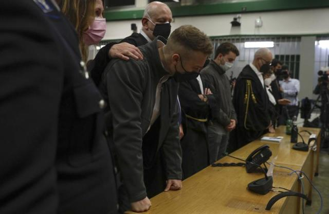 """FILE - In this Wednesday, May 5, 2021 file photo, Finnegan Lee Elder, foreground, listens as the verdict is read, in the trial for the slaying of an Italian plainclothes police officer on a street near the hotel where he and his co-defendant Gabriel Natale-Hjorth were staying while on vacation in Rome in summer 2019, in Rome. Several professional associations for Italian criminal defense lawyers are slamming a Rome court's unusual attack on the team defending two U.S. young men in the trial for the murder of an Italian police officer. Last week, the court, in explaining its May 5 convictions and life sentences for Finnegan Lee Elder, 21, and Gabriel Natale-Hjorhy 20, blasted defense lawyers for effectively trying to sow doubt about the credibility of the plainclothes partner of Carabinieri Vice Brigadiere Mario Cerciello Rega. The officer died after being stabbed 11 times near the Americans' hotel in 2019. One lobby group said the court sounded as if it had """"decided beforehand"""" the trial's outcome. (AP Photo/Gregorio Borgia, File)"""
