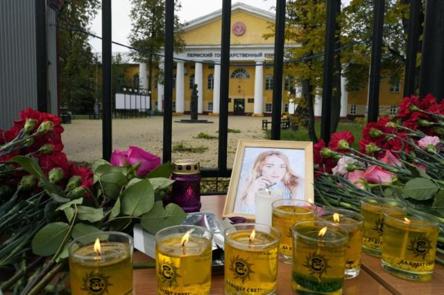 Flowers, candles and a portrait of one of victims are displayed on a table outside the Perm State University in Perm, about 1,100 kilometers (700 miles) east of Moscow, Russia, Tuesday, Sept. 21, 2021. A student opened fire at the university, leaving a number of people dead and injured, before being shot in a crossfire with police and detained. Beyond saying that he was a student, authorities offered no further information on his identity or a possible motive. (AP Photo/Dmitri Lovetsky)