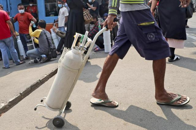 A man leaves with his full oxygen canister as others wait to refill their tanks at a recharging station in Jakarta, Indonesia, Friday, July 9, 2021. Just two months ago, Indonesia was coming to a gasping India's aid with thousands tanks of oxygen. Now, the Southeast Asia country is running out of oxygen as it endures a devastating wave of coronavirus cases and the government is seeking emergency supplies from other countries, including Singapore and China. (AP Photo/Tatan Syuflana)
