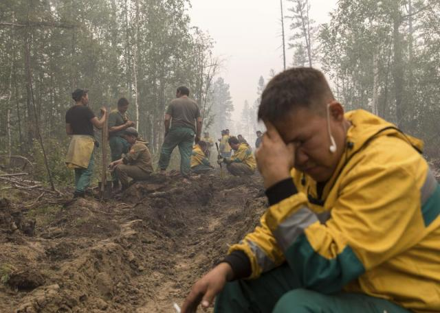Employees of the Yakutlesresurs rest as they dig a firebreak moat to stop a forest fire outside Magaras village 87 km. (61 miles) west of Yakustk, the capital of the republic of Sakha also known as Yakutia, Russia Far East, Sunday, July 18, 2021. Russia has been plagued by widespread forest fires, blamed on unusually high temperatures and the neglect of fire safety rules, with the Sakha-Yakutia region in northeastern Siberia being the worst affected. (AP Photo/Alexey Vasilyev)