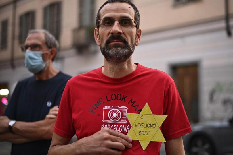 """FILE - In this Wednesday, July 28, 2021 file photo, a man shows a sign shaped like a Star of David reading in Italian """"They want us like this"""" during a protest against the COVID-19 vaccination pass in Turin, Italy. Shouts of """"liberty"""" have echoed through Italian and French streets and squares as thousands show their opposition to plans to require vaccination cards to continue normal social activities, like dining indoors at restaurants, visiting museums or cheering home teams in stadiums. (Marco Alpozzi/LaPresse via AP, File)"""