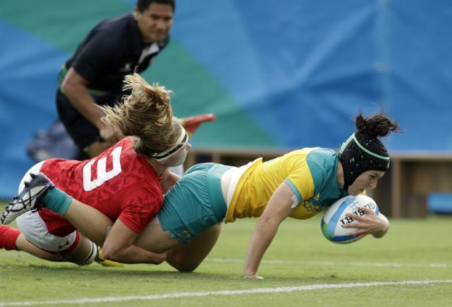 FILE - In this Aug. 8, 2016, file photo, Australia's Emilee Cherry, right, scores a try as Canada's Karen Paquin, defends during the women's rugby sevens semi final match at the Summer Olympics in Rio de Janeiro, Brazil. Cherry, the former women's sevens player of the year who gave birth to a daughter in 2019 announced Friday, May 28, 2021, that she's retiring and won't be in the Australian team when the Tokyo Olympic Games begin on July 23. (AP Photo/Themba Hadebe, File)