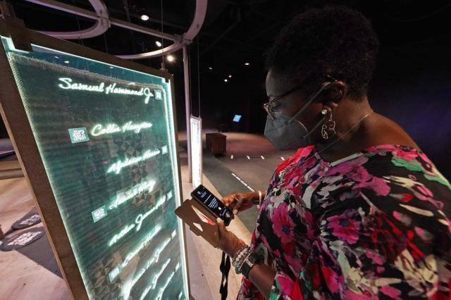 """Pamela D.C. Junior, director of the Two Mississippi Museums in Jackson, searches for a specific cold case selection at the PBS Frontline's traveling augmented-reality exhibit, """"Un(re)solved"""" in the museum's special exhibit room, Friday, Aug. 27, 2021. The exhibit was opened on Saturday, Aug. 28, to align with the commemoration of the death of Emmett Till, a Chicago teenager who was lynched in Mississippi in 1955. The multi-media platform examines the federal government's efforts to investigate more than 150 civil rights era cold cases on the Emmett Till Unsolved Civil Rights Crime Act. (AP Photo/Rogelio V. Solis)"""
