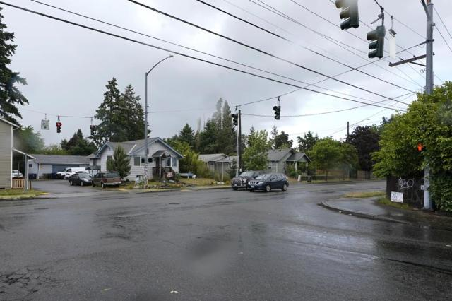"""Cars stop at a traffic light, Thursday, May 27, 2021, near at a memorial that has been established at the intersection in Tacoma, Wash., south of Seattle, where Manuel """"Manny"""" Ellis died on March 3, 2020, after he was restrained by police officers. Earlier in the day, the Washington state attorney general filed criminal charges against three police officers in the death of Ellis, a Black man who died after telling the Tacoma officers who were restraining him he couldn't breathe. (AP Photo/Ted S. Warren)"""