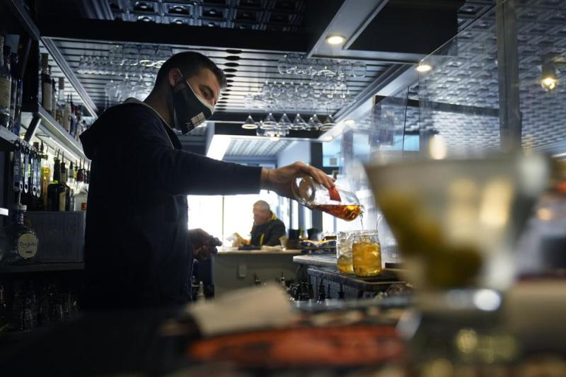 ARCHIVO - En esta fotografía de archivo del 6 de abril de 2021, el barman Denis Angelov, con mascarilla para protegerse del coronavirus, prepara una bebida en el restaurante Tin Pan Alley en Provincetown, Massachusetts. (AP Foto/Steven Senne, archivo)